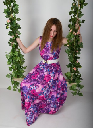 leggy: Beautiful young leggy redhaired woman in a long colorful dress on a swing, wooden swing suspended from a rope hemp, rope wrapped vine and ivy.