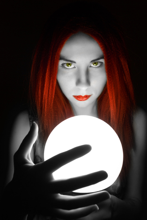 adivino: Magnificent Redhead fortune teller holding crystal ball. beautiful woman tries to look into the future. Foto de archivo