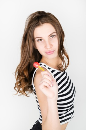 tweens: beautiful slim girl in black shorts and a striped top, eating candy. closeup lip licking candy. Stock Photo