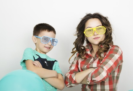 to fold one's arms: brother and sister, wearing glasses in the style of disco. fold ones arms.