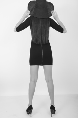 leggy: Beautiful young leggy brunette in a little black dress and big black hat, back view. black and white.