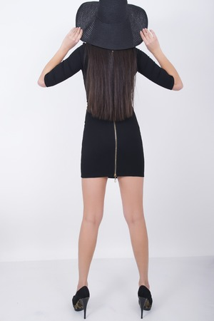 leggy: Beautiful young leggy brunette in a little black dress and big black hat, back view.