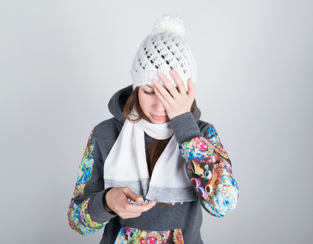 throbbing: young woman in a knitted hat and scarf, holding hands in the thermometer. she seems sick. holding his head Stock Photo
