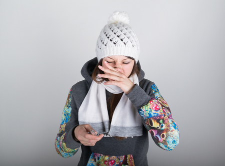 throbbing: young woman in a knitted hat and scarf, holding hands in the thermometer. she seems sick. scratching your nose, wipe the snot