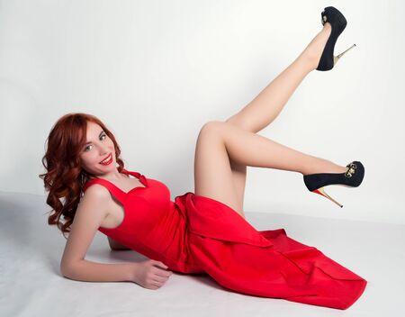 footsie: Elegant young redhead woman in a red dress and black high heels, lying on his back and put his feet up.