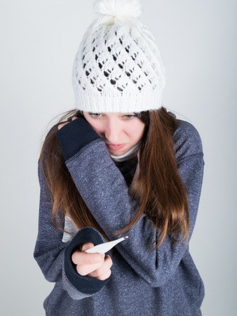 throbbing: young woman in a knitted hat and scarf, holding hands in the thermometer. she seems sick.