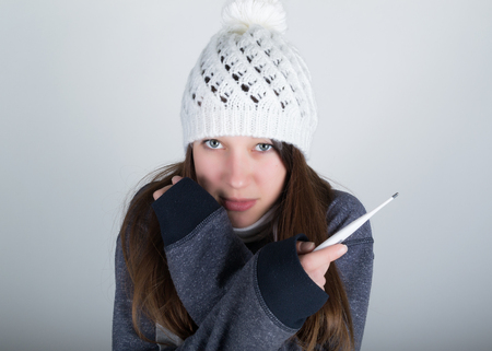 pissed: young woman in a knitted hat and scarf, holding hands in the thermometer. she seems sick.