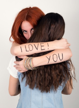 trait: red-haired girl hugging her friend in her arms the inscription I love you.