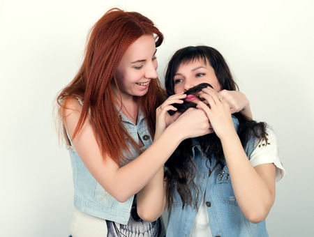 indulge: Two young girlfriends indulge and grimace, make each other a mustache out of the hair. Teenager making moustache from hair. Stock Photo