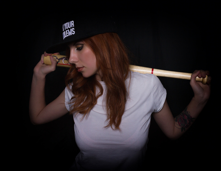 young teenager girl in a white shirt and black cap, posing with a baseball bat. play of light and shadows.