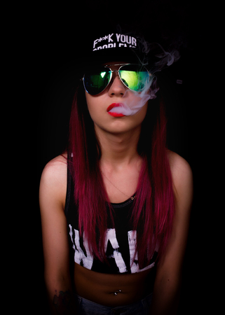 rapper: Attractive young woman in cap and sunglasses, smokes on a dark background. Be trendy, be rapper. Stock Photo