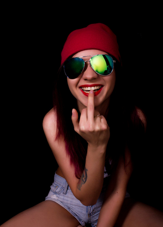 finger licking: Attractive young woman in a pink knitted cap and sunglasses, licking her middle finger on a dark background.