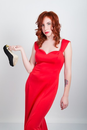 debauch: Beautiful young sexy slim red-haired girl wearing a slinky silk red dress high heels, in alcoholic intoxication. drinking red wine from a glass. after party.
