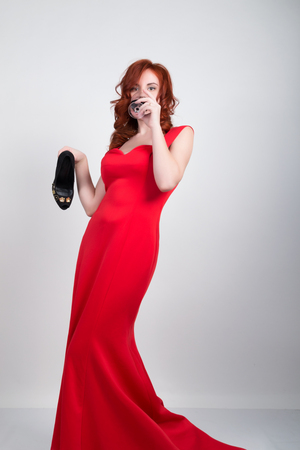 slinky: Beautiful young sexy slim red-haired girl wearing a slinky silk red dress high heels, in alcoholic intoxication. drinking red wine from a glass. after party.