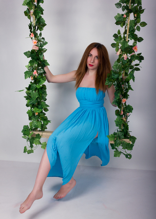 leggy: Beautiful young leggy redhaired woman in a long blue dress on a swing, wooden swing suspended from a rope hemp, rope wrapped vine and ivy.