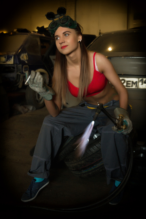 blowpipe: Girl mechanic sitting on a tire with blowpipe smoking in a garage.