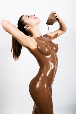 relax massage: young girl in the spa salon she pours on her body the chocolate, chocolate body wrap treatment, skin rejuvenation. Beauty treatment concept. Stock Photo
