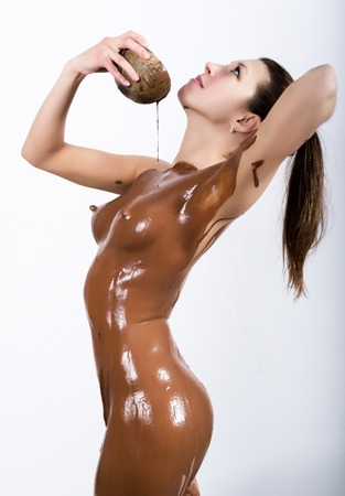 young girl in the spa salon she pours on her body the chocolate, chocolate body wrap treatment, skin rejuvenation. Beauty treatment concept. Stock Photo