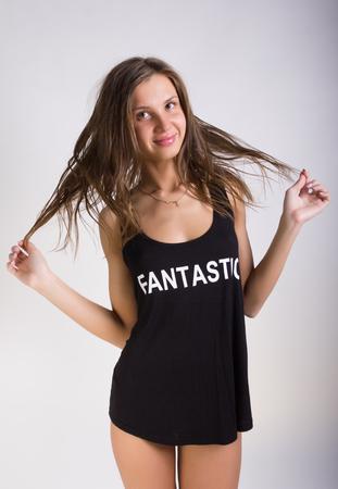 Fille sexy dans un T-shirt noir sur son nu posant corps. Banque d'images - 55353789