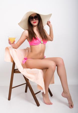 grosse fesse: belle fille en bikini, lunettes de soleil et un grand chapeau assis sur une chaise longue, tenant sa main avec un verre de cocktail.
