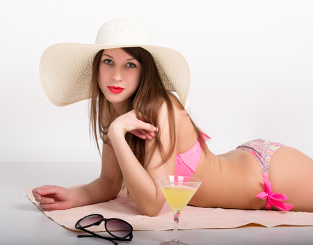 grosse fesse: belle fille en bikini, lunettes de soleil et un grand chapeau allong� sur la serviette de plage debout � c�t� d'un verre de cocktail.