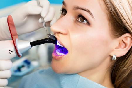 Der Empfang war bei den weiblichen Zahnarzt. Arzt untersucht die Mundhöhle auf Karies. Kariesschutz. Karies-Behandlung. Zahnarzt arbeiten mit Zahn Polymerisationsleuchte in der Mundhöhle. Standard-Bild
