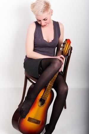 hugging legs: Drunken blonde woman sitting on a chair, lowered stockings legs hugging guitar. Stock Photo
