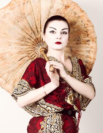 geisha kimono: beautiful girl dressed as a geisha girl holding a Chinese umbrella. Geisha makeup and hair dressed in a kimono. The concept of traditional Japanese values.