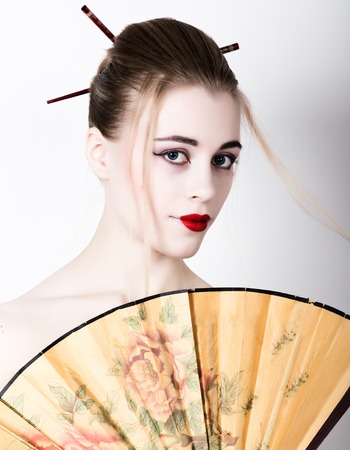 geisha kimono: beautiful girl dressed as a geisha, she holds a chinese fan. Geisha makeup and hair dressed in a kimono. The concept of traditional Japanese values.