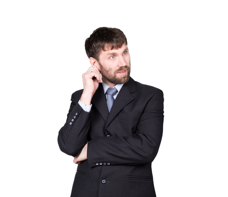 nonverbal communication: gestures distrust lies. body language. man in business suit, scratching, rubbing the ear. isolated on white background. concept of true or false.