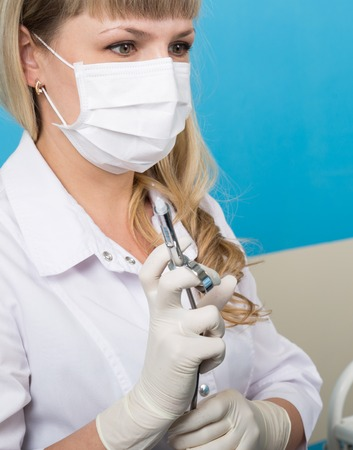 anesthetic: The reception was at the female dentist. Doctor examines the oral cavity on tooth decay. Caries protection. doctor puts the patient an anesthetic injection. close-up portrait of the doctor with a syringe. Stock Photo