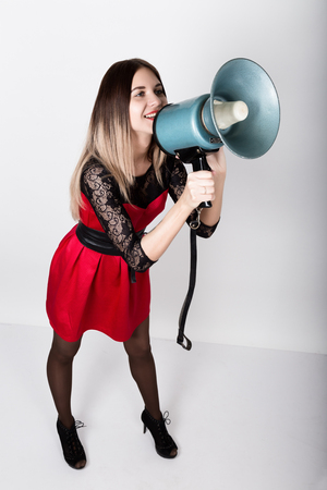 yells: leggy beautiful girl in a red dress with lace sleeves, she yells into a bullhorn. Public Relations.