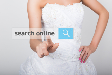 technology, internet and networking concept. Beautiful bride in fashion wedding dress. Bride presses search online button on virtual screens.