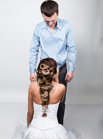 knelt: beautiful young couple in love, bride knelt before the groom. provocation playful couple.