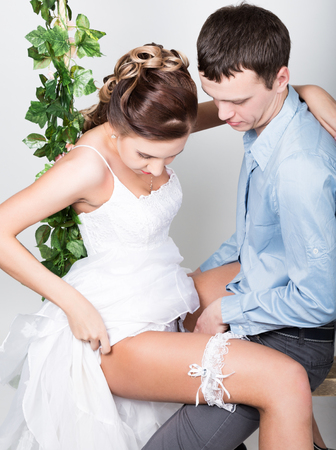 hugging legs: closeup of a young couple in love, man stands with his back to the camera, she bites his ear. Playful couple. her legs hugging man. Stock Photo
