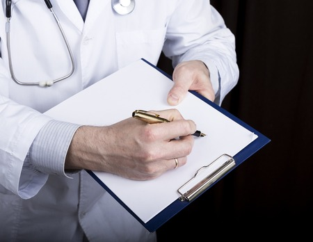 patient data: close-up hands of a medical doctor, the doctor signs a handle documents. Doctor writes medical history. write a prescription patient data history.