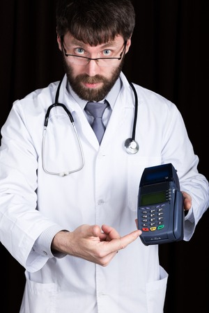 high cost: close-up portrait of a medical doctor, he proposes to pay for treatment in pos-terminal. concept of high cost of the treatment. Stock Photo