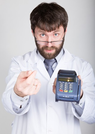 proposes: close-up portrait of a medical doctor, he proposes to pay for treatment in pos-terminal. concept of high cost of the treatment. Stock Photo