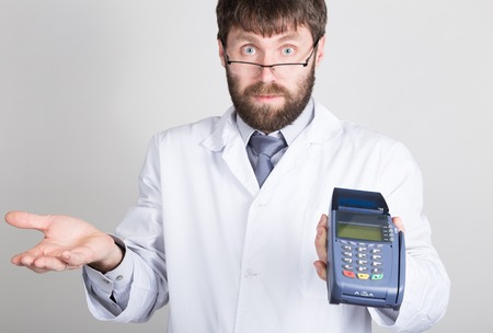 take a history: close-up portrait of a medical doctor, he proposes to pay for treatment in pos-terminal. concept of high cost of the treatment. Stock Photo
