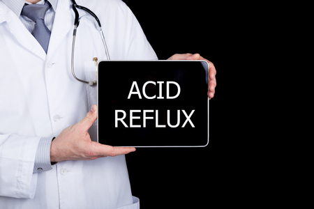 acid reflux: technology, internet and networking in medicine concept - Doctor holding a tablet pc with acid reflux sign. Internet technologies in medicine. Stock Photo