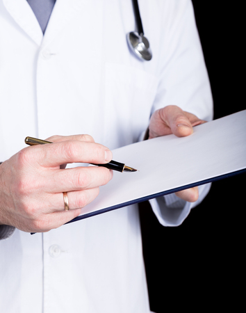 patient's history: close-up hands of a doctor, he takes notes in a patients medical history.
