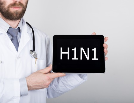 h1n1: technology, internet and networking in medicine concept - Doctor holding a tablet pc with h1n1 sign. Internet technologies in medicine.