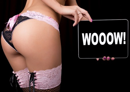 technology, internet and networking - close-up ass of girl in lacy lingerie, holding a tablet pc with wooow sign. Adult content.