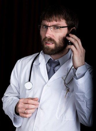 Dr. bearded manin a white medical robe, stethoscope on his neck, emotionally talking on phone.