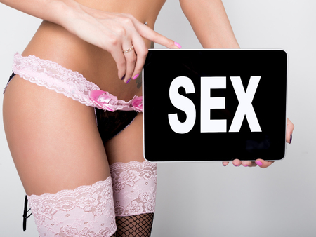 adult sex: technology, internet and networking - close-up ass of girl in lacy lingerie, holding a tablet pc with sex sign. Adult content.