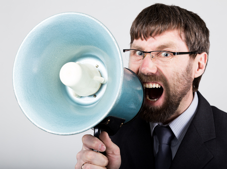 amplified: bearded businessman yelling through bullhorn. Public Relations. man expresses various emotions. photos of young businessman wearing a suit and tie. Stock Photo