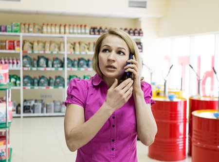 motor oil: blonde girl chooses motor oil in auto parts store. consults by phone Stock Photo