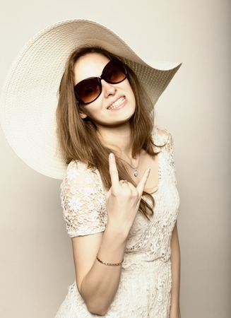 expresses: beautiful girl in broad-brimmed hat and sunglasses posing and expresses different emotions.