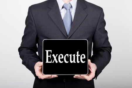 execute: technology, internet and networking in business concept - businessman holding a tablet pc with execute sign. Internet technologies in business. Stock Photo