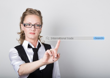 international internet: international trade written in search bar on virtual screen. technology, internet and networking concept. Internet technologies in business and home. woman in business suit and tie, presses a finger on a virtual screen. Stock Photo